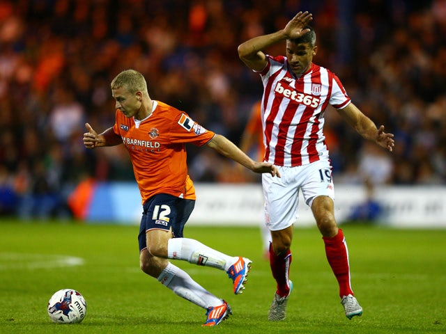Scott Griffiths of Luton Town is closed down by Jonathan Walters of Stoke City during the Capital One Cup second round match between Luton Town and Stoke City at Kenilworth Road on August 25, 2015