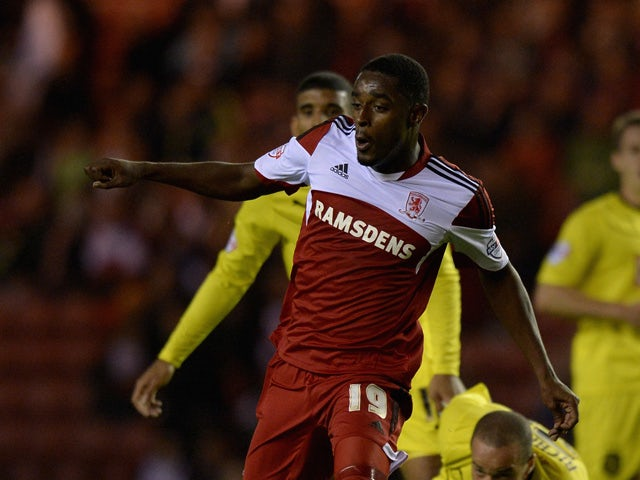 Mustapha Carayol of Middlesbrough gets past Jazz Richards of Huddersfield during the Sky Bet Championship match between Middlesbrough and Huddersfield Town at Riverside Stadium on October 01, 2013
