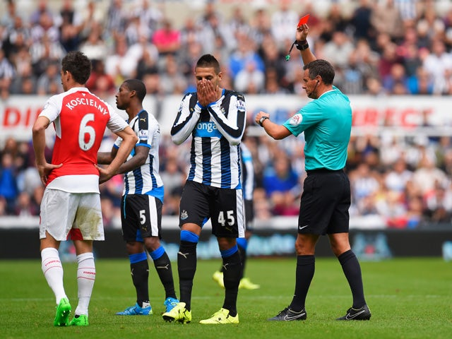 Aleksandar Mitrovic of Newcastle United is shown a red card by referee Andre Marriner (1st R) during the Barclays Premier League match between Newcastle United and Arsenal at St James' Park on August 29, 2015