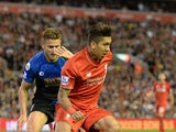 Liverpool's Brazilian midfielder Roberto Firmino (R) is challenged by Bournemouth's English defender Simon Francis during the English Premier League football match between Liverpool and Bournemouth at the Anfield stadium in Liverpool, north-west England o