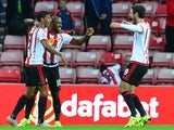 Jermain Defoe of Sunderland celebrates scoring the opening goal with team mate Patrick Van Anholt during the Capital One Cup Second Round match between Sunderland and Exeter City at Stadium of Light on August 25, 2015