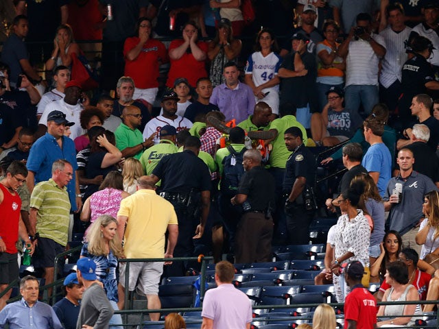 Emergency medical staff help a fan that fell from the upper deck of Turner Field during the game between the Atlanta Braves and the New York Yankees on August 29, 2015