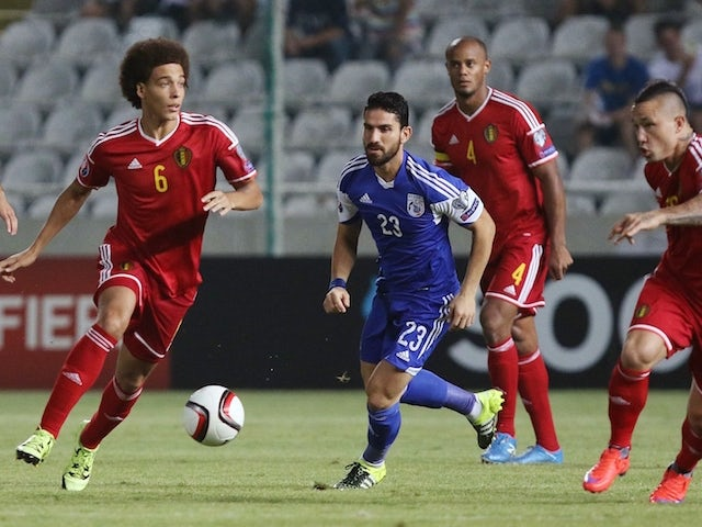 Belgium's Axel Witsel (L) runs with the ball as Cyprus' Marios Nikolaou (C) defends during the EURO 2016 qualifier football match between Cyprus and Belgium at the Neo GSP stadium in the Cypriot capital, Nicosia, on September 6, 2015.