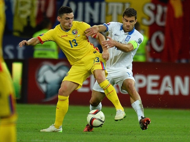 Claudiu Keseru (L) of Romania vies for the ball with Sokratis Papastathopoulos (R) of Greece during the UEFA Euro 2016 qualifying football match between Romania and Greece, in Bucharest, Romania on September 7, 2015.