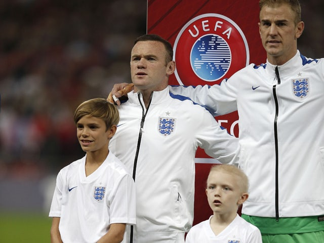 Romeo Beckham, son of former England footballer David Beckham, stands with England's striker Wayne Rooney as the team sing the national anthem ahead of the Euro 2016 qualifying group E football match between England and Switzerland at Wembley Stadium in w