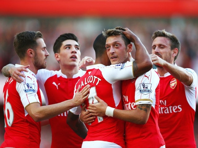 Theo Walcott is congratulated by teammates after scoring Arsenal's opener against Stoke on September 12, 2015