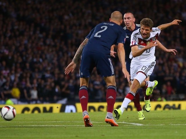 Germany's midfielder Thomas Muller (R) shoots to score the opening goal of the Euro 2016 qualifying group D football match between Scotland and Germany at Hampden Park in Glasgow on September 7, 2015