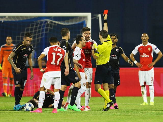 Olivier Giroud of Arsenal is shown the red card by referee Ovidiu Hategan during the UEFA Champions League Group F match between Dinamo Zagreb and Arsenal at Maksimir Stadium on September 16, 2015