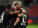 Leverkusen's midfielder Hakan Calhanoglu celebrates scoring with Slovenian midfielder Kevin Kampl (R) and Brazilian defender Wendell during the UEFA Champions League group E first leg football match between Bayer 04 Leverkusen and FC Bate Borisov in Lever
