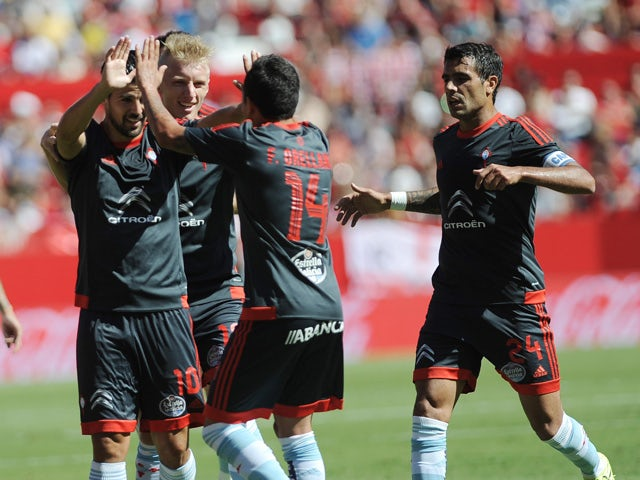 Celta Vigo's forward Nolito (L) celebrates a goal with teammates during the Spanish league football match Sevilla FC vs Celta de Vigo at the Ramon Sanchez Pizjuan stadium in Sevilla on September 20, 2015