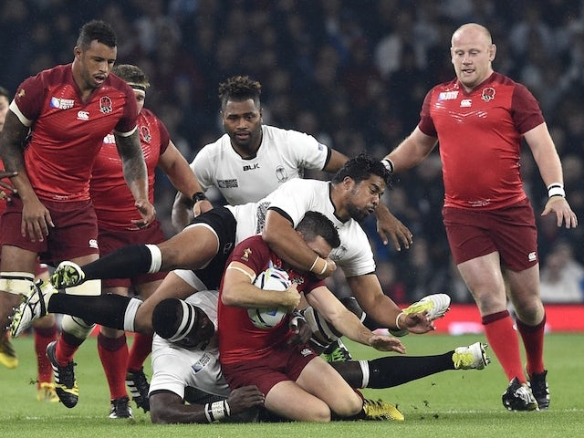 England's fly-half George Ford (C) is tackled during a Pool A match of the 2015 Rugby World Cup between England and Fiji at Twickenham stadium in south west London on September 18, 2015.