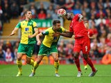 Christian Benteke of Liverpool heads the ball under pressure from Steven Whittaker (L) and Russell Martin of Norwich City during the Barclays Premier League match between Liverpool and Norwich City at Anfield on September 20, 2015