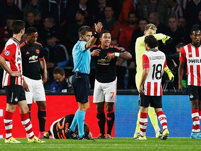 Luke Shaw of Manchester United lies on the ground injured as referee Nicola Rizzoli calls for medical assistance during the UEFA Champions League Group B match between PSV Eindhoven and Manchester United at PSV Stadion on September 15, 2015