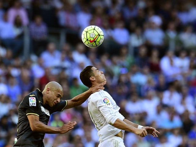 Real Madrid's Portuguese forward Cristiano Ronaldo (R) vies with Granada's Brazilian defender Doria during the Spanish league football match Real Madrid CF vs Granada FC at the Santiago Bernabeu stadium in Madrid on Spetember 19, 2015