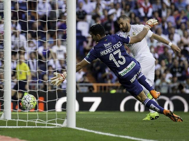 Karim Benzema (R) of Real Madrid CF scores their opening goal against goalkeeper Andres Fernandez (L) of Granada CF during the La Liga match between Real Madrid CF and Granada CF at Estadio Santiago Bernabeu on September 19, 2015