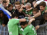 Saint-Etienne's French forward Jonathan Bamba celebrates with teammates and supporters after scoring a goal during the French Ligue 1 football match between AS Saint-Etienne and FC Nantes on September 20, 2015