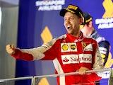 Sebastian Vettel of Germany and Ferrari celebrates on the podium after winning the Formula One Grand Prix of Singapore at Marina Bay Street Circuit on September 20, 2015