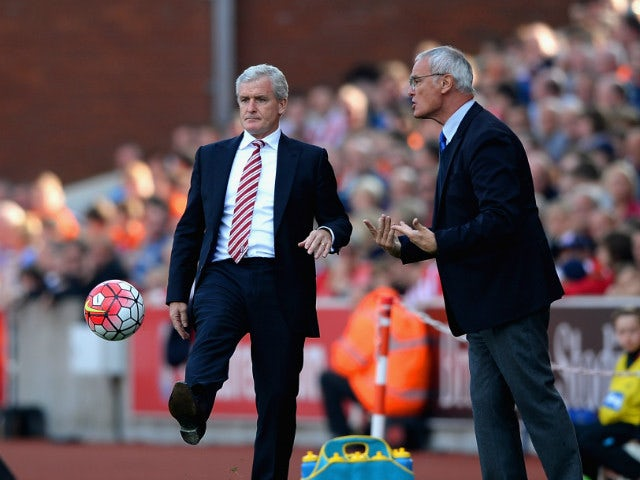 Mark Hughes manager of Stoke City kicks the ball while Claudio Ranieri Manager of Leicester City instructs his players during the Barclays Premier League match between Stoke City and Leicester City at Britannia Stadium on September 19, 2015 in Stoke on Tr