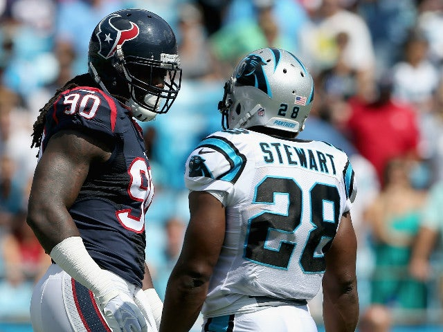 Jonathan Stewart #28 of the Carolina Panthers exchanges words with Jadeveon Clowney #90 of the Houston Texans in the first quarter during their game at Bank of America Stadium on September 20, 2015 in Charlotte, North Carolina.