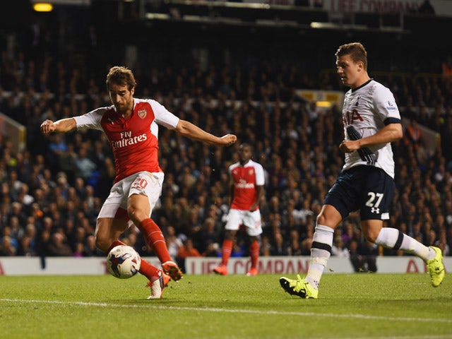 Mathieu Flamini of Arsenal scores their first goal as Kevin Wimmer of Tottenham Hotspur looks on during the Capital One Cup third round match between Tottenham Hotspur and Arsenal at White Hart Lane on September 23, 2015