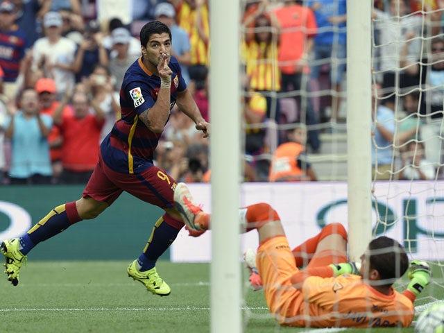 :Barcelona's Uruguayan forward Luis Suarez celebrates after scoring a goal during the Spanish league football match FC Barcelona vs UD Las Palmas at the Camp Nou stadium in Barcelona on September 26, 2015.