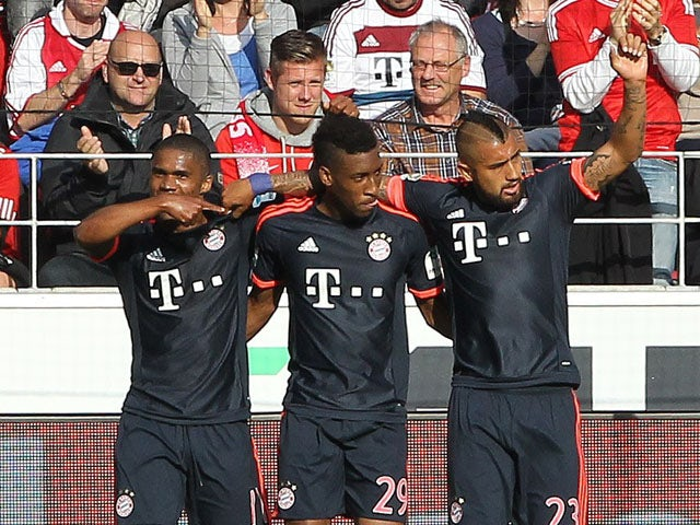Bayern Munich's French forward Kingsley Coman (L) celebrates scoring the 3-0 with Bayern Munich's Brazilian midfielder Douglas Costa (L) and Bayern Munich's Chilean midfielder Arturo Vidal during the German first division Bundesliga football match 1 FSV M