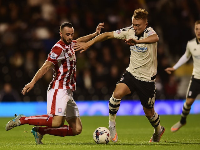 Cauley Woodrow of Fulham is tackled by Marc Wilson of Stoke City during the Capital One Cup Third Round match between Fulham and Stoke City at Craven Cottage on September 22, 2015 in London, United Kingdom.