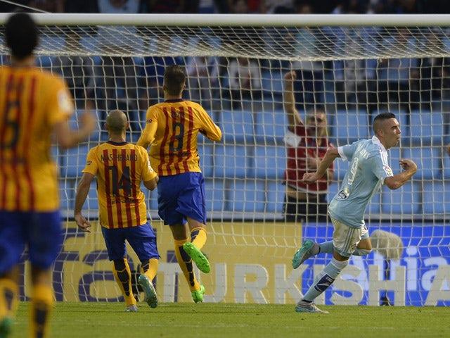 Celta Vigo's forward Iago Aspas (R) celebrates after scoring a goal during the Spanish league football match Celta Vigo vs FC Barcelona at the Balaidos stadium in Vigo on September 23, 2015