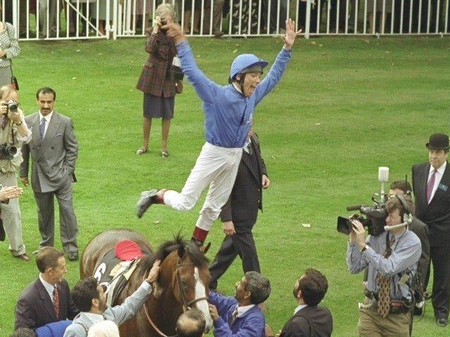 Frankie Dettori leaps off of Mark of Esteem after winning the Queen Elizabeth the II stakes during his unique achievment of winning all seven races on the card at Ascot in England
