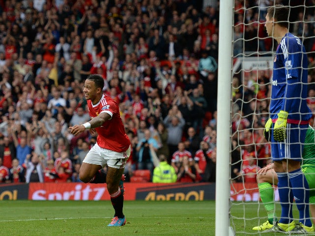 Manchester United's Dutch midfielder Memphis Depay (L) celebrates scoring the opening goal as Sunderland's Romanian goalkeeper Costel Pantilimon (R) looks on during the English Premier League football match between Manchester United and Sunderland at Old