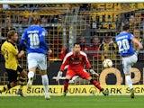 Darmstadt's midfielder Marcel Heller (R) scores past Dortmund's Swiss goalkeeper Roman Buerki during the German first division Bundesliga football match Borussia Dortmund v SV Darmstadt 98, in Dortmund, western Germany, on September 27, 2015