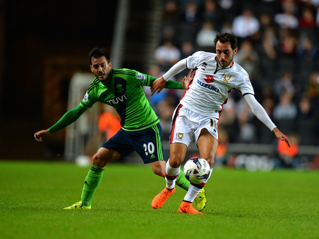 Sergio Aguza of MK Dons is tackled by Juanmi of Southampton during the Capital One Cup third round match between MK Dons and Southampton at Stadium mk on September 23, 2015