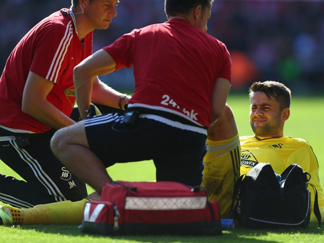Lukasz Fabianski of Swansea City receives a medical treatment during the Barclays Premier League match between Southampton and Swansea City at St Mary's Stadium on September 26, 2015