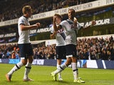 Nacer Chadli of Tottenham Hotspur (R) celebrates with Tommy Carroll (C) and Harry Kane (L) as Calum Chambers of Arsenal scores an own goal foe their first goal during the Capital One Cup third round match between Tottenham Hotspur and Arsenal at White Har
