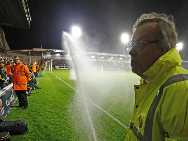 A safety steward tries to stop the pitch watering system as it comes on during the English League Cup third round football match between Walsall and Chelsea at The Banks's Stadium in Walsall, central England on September 23, 2015