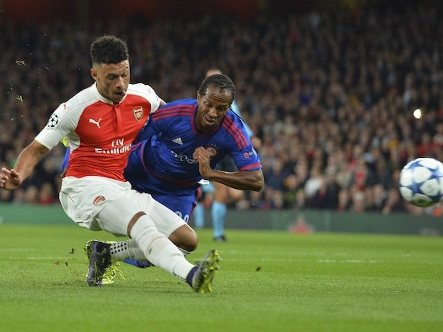 Arsenal's English midfielder Alex Oxlade-Chamberlain (L) shoots but hits the side netting and misses the chance under pressure from Olympiakos's Brazilian defender Leandro Salino (R) during the UEFA Champions League Group F football match between Arsenal