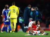 Alex Oxlade-Chamberlain of Arsenal sits dejected after the UEFA Champions League Group F match between Arsenal FC and Olympiacos FC at the Emirates Stadium on September 29, 2015 in London, United Kingdom.