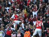 Arsenal's Chilean striker Alexis Sanchez (C) celebrates scoring his goal with team mates Arsenal's German midfielder Arsenal's English midfielder Theo Walcott (L) during the English Premier League football match between Arsenal and Manchester United at th