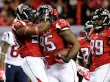 Jonathan Babineaux #95 celebrates with O'Brien Schofield #50 of the Atlanta Falcons after an interception in the first half against the Houston Texans at the Georgia Dome on October 4, 2015