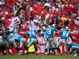 Graham Gano #9 of the Carolina Panthers kicks an extra point as Tony McDaniel #77 and Kwon Alexander #58 of the Tampa Bay Buccaneers defend during the first quarter of the game at Raymond James Stadium on October 4, 2015