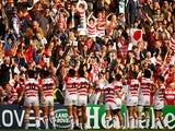 Japan fans celebrate with players after the 2015 Rugby World Cup Pool B match between Samoa and Japan at Stadium mk on October 3, 2015