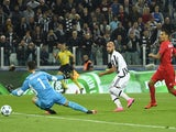 Juventus' forward from Italy Simone Zaza (C) scores against Sevilla's goalkeeper Sergio Rico Gonzalez during the UEFA Champions League football match Juventus vs FC Sevilla on September 30, 2015