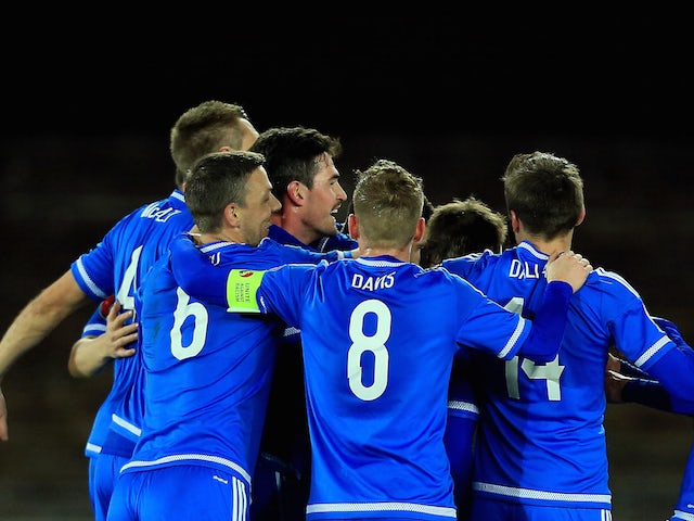 Craig Cathcart of Northern Ireland is mobbed after scoring the opening goal during the UEFA EURO 2016 Qualifying match between Finland and Northern Ireland at the Olympic Stadium on October 11, 2015 in Helsinki, Finland.