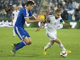 Israeli's midfielder Nir Bitton (L) defends against Cyprus' midfielder Constantinos Makridis (R) during their Euro 2016 qualifying football match between Israel and Cyprus at the Teddy Kollek Memorial Stadium in the city of Jerusalem, on October 10, 2015.