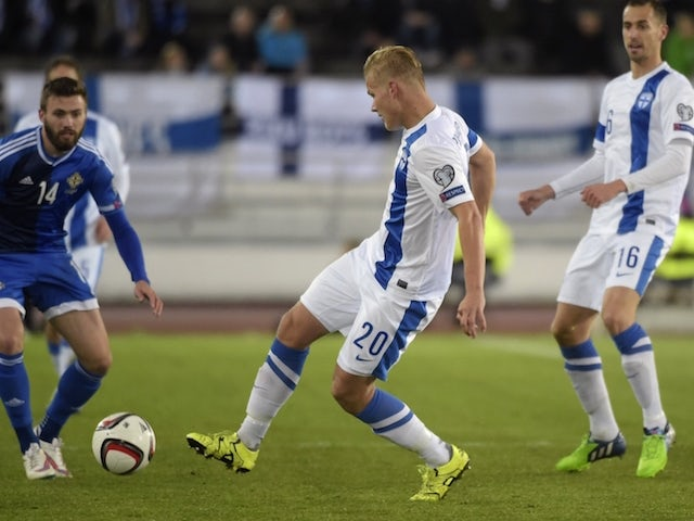 Stuart Dallas (L) of Northern Ireland and Joel Pohjanpalo (C) and Sakari Mattila (R) of Finland vie for the ball during the Euro 2016 Group F qualifying football match between Finland and Northern Ireland at the Helsingin Olympiastadion in Helsinki on Oct