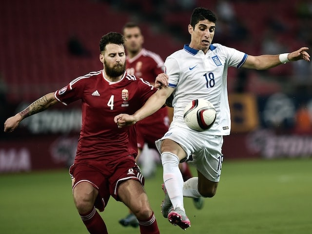 Greece's Petros Mantalos (R) vies for the ball with Hungary's Tamas Kadar during the UEFA Euro 2016 qualifying Group F football match between Greece and Hungary at the Stadio Georgios Karaiskakis in Athens on October 11, 2015.