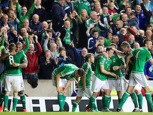 Northern Ireland's midfielder Steven Davis (L) celebrates with teammates after scoring the opening goal during the UEFA Euro 2016 qualifying Group F football match between Northern Ireland and Greece at Windsor Park in Belfast, Northern Ireland, on Octobe