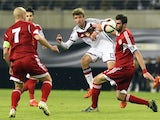 Germany's midfielder Thomas Mueller (C) and Georgia's defender Solomon Kverkvelia (R) vie for the ball during the Euro 2016 Group D qualifying football match between Germany and Georgia in Leipzig, eastern Germany, on October 11, 2015.