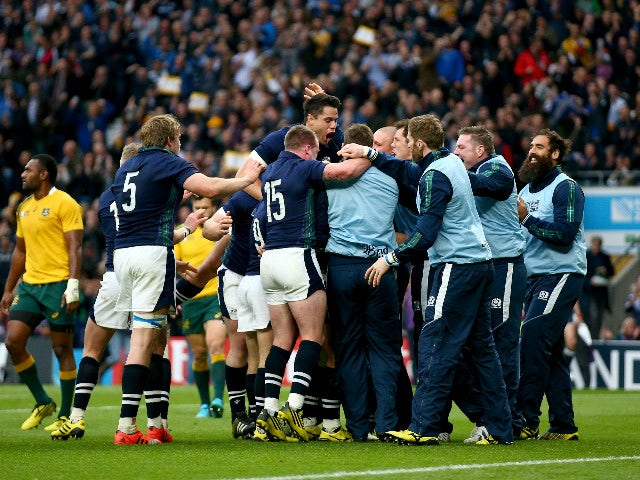 Scotland players and substitutes mob try scorer Peter Horne of Scotland during the 2015 Rugby World Cup Quarter Final match between Australia and Scotland at Twickenham Stadium on October 18, 2015 in London, United Kingdom.