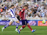 Atletico Madrid's French forward Antoine Griezmann (R) shoot to score next to Real Sociedad's defender Inigo Martinez (L) during the Spanish league football match Real Sociedad de Futbol vs Club Atletico de Madrid at the Anoeta stadium in San Sebastian on